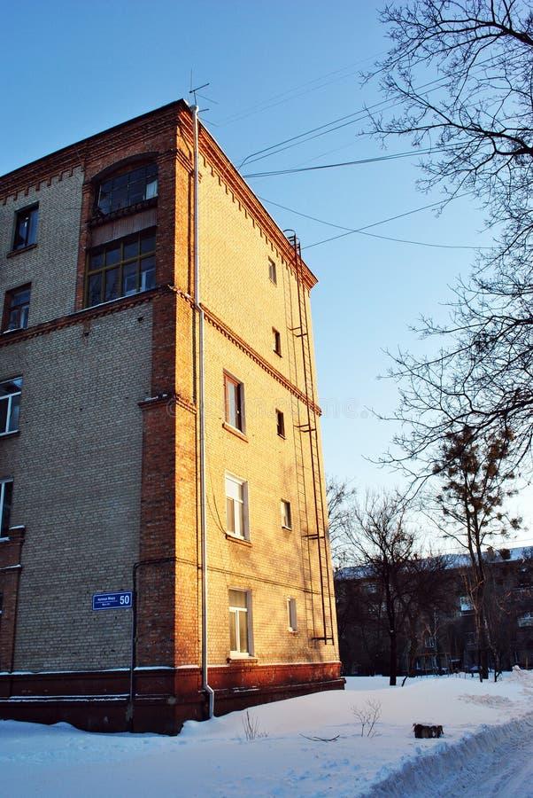 Cegła kąt budynek mieszkalny z okno i drainpipe, zimna śnieżna pogodna zimy ulica zdjęcie royalty free