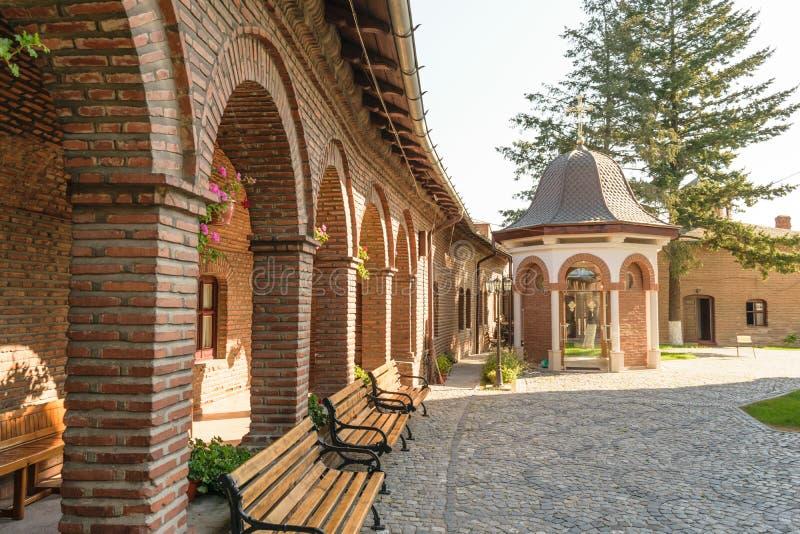 Ceglane arkady, drewno ławki w powierzchowność sądzie Plumbuita monaster, Bucharest, Rumunia zdjęcia royalty free