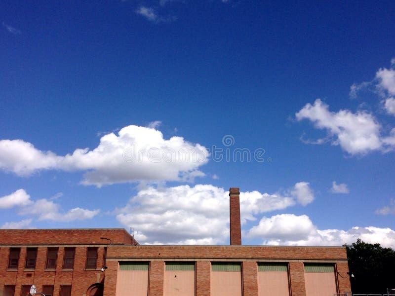 Ceglany Dom z Smokestack i Błękitnym Chmurnym niebem zdjęcie royalty free