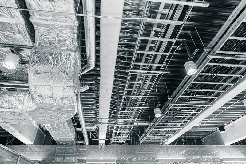 Ceiling air pipe air ventilation and manged data cables. In a cableway on the office roof royalty free stock photo
