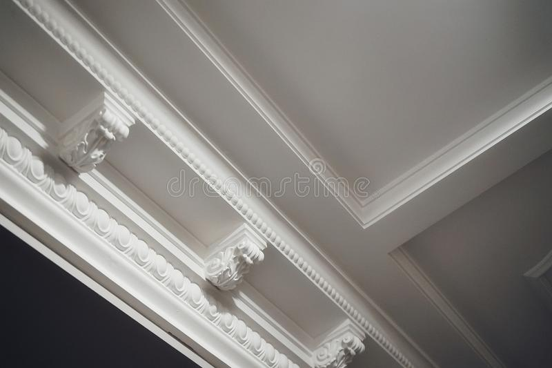 Ceiling decor architecture white color luxury light textured fretwork molding. Ceiling decor architecture white color luxury light textured close-up molding stock image
