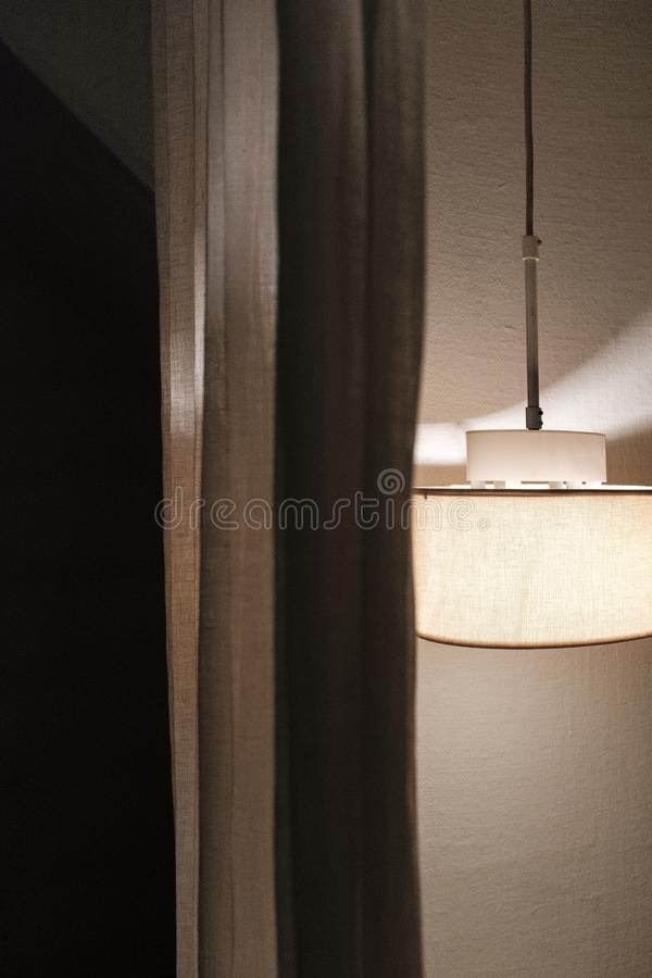 A ceiling lamp next to a curtain royalty free stock photo
