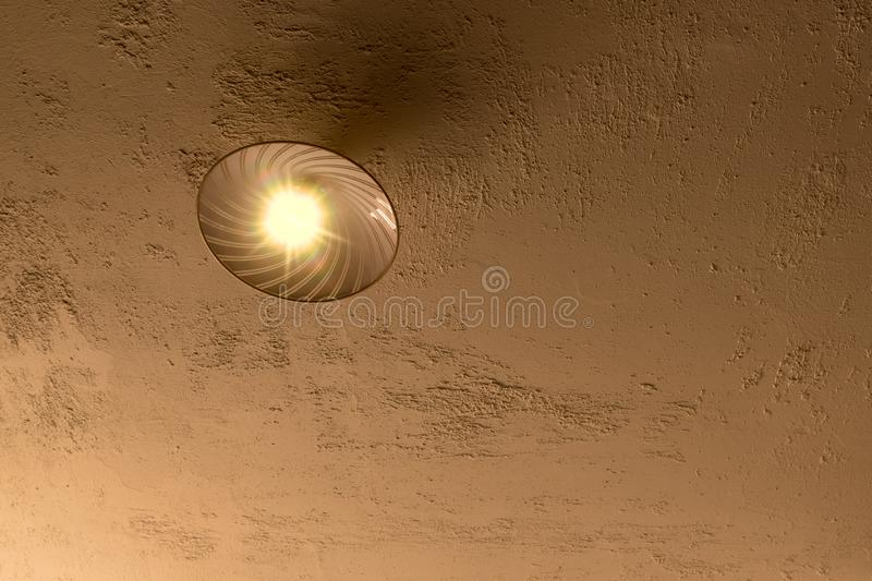 A ceiling lamp on a rough plastered concrete ceiling royalty free stock photo