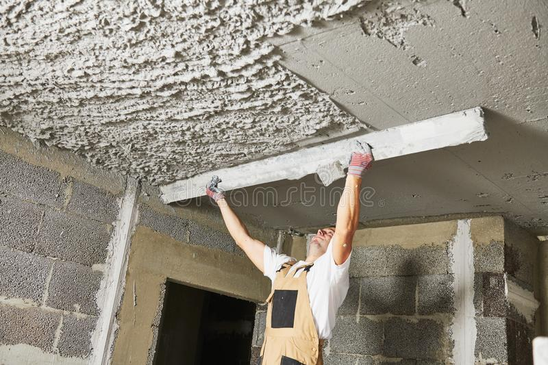 Plasterer smoothing plaster mortar on ceiling with screeder royalty free stock photo