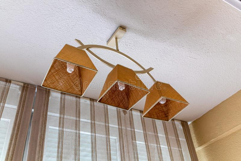Ceiling sand lamp from white ceiling and beige courtains stock photography