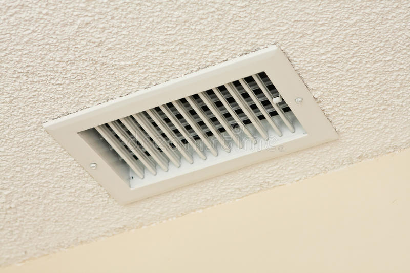 Ceiling vent on acoustic ceiling. A new heating and air conditioning vent on a white acoustic ceiling royalty free stock image