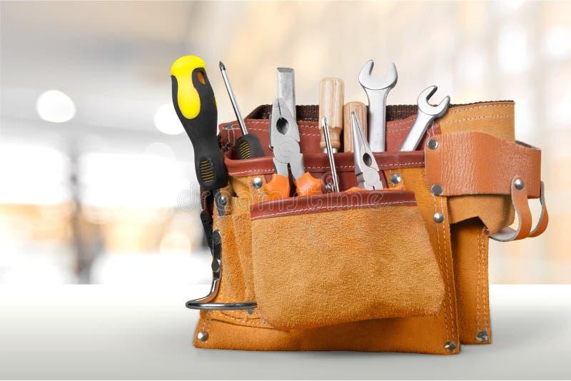 Ceinture d'outil avec des outils sur le fond clair image stock