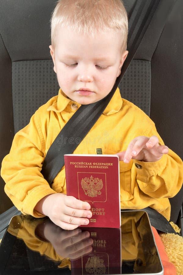 Ceinture de sécurité, passeport Un petit enfant heureux s'assied dans le siège de voiture dans le passeport d'un citoyen russe Le photo stock