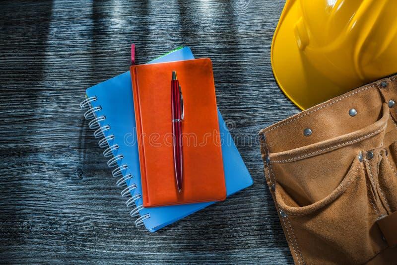 Ceinture en cuir d'outil de chapeau de sécurité de stylo de carnets sur le conseil en bois photos libres de droits