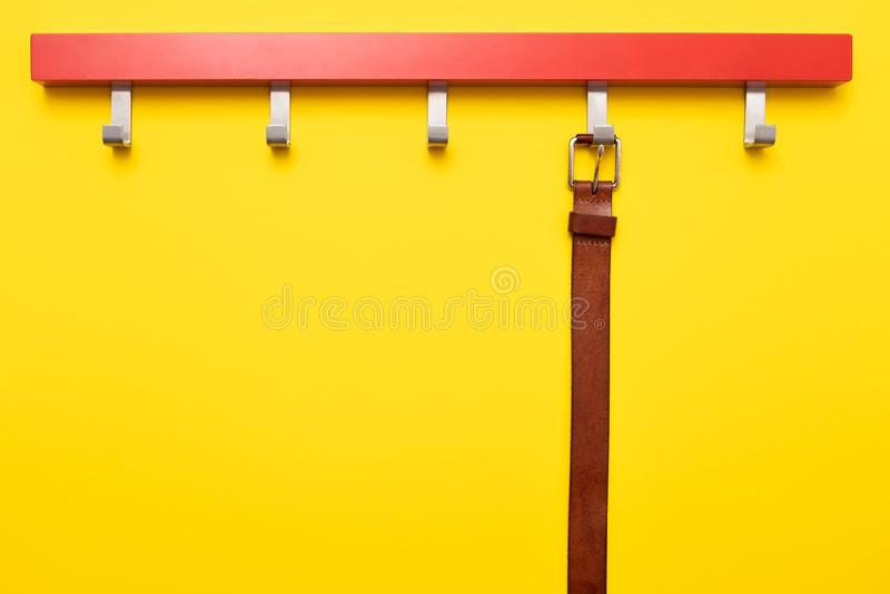 Ceinture en cuir masculine sur le cintre sur le fond jaune images libres de droits