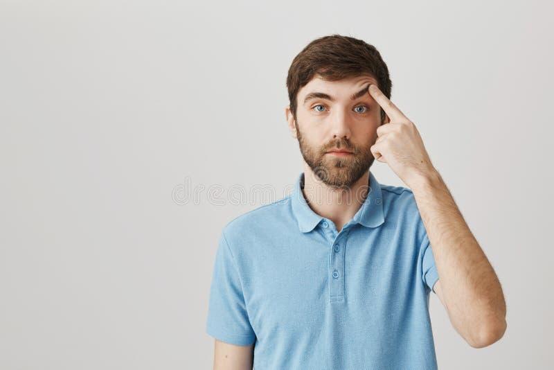 Ceja de elevación masculina barbuda europea apuesta tranquila con el dedo índice y situación con la cara de póker sobre gris imagenes de archivo
