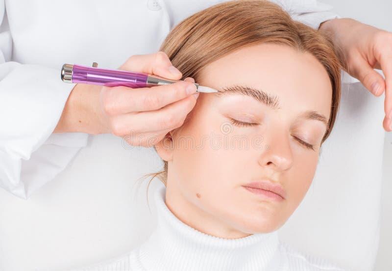 Cejas de Microblading Mujer atractiva que consigue cuidado facial y maquillaje permanente imagenes de archivo