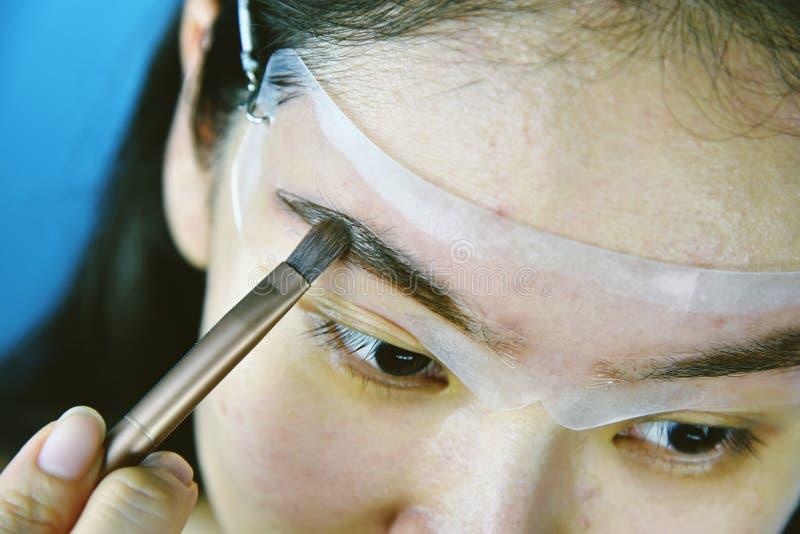 Cejas que forman la plantilla del maquillaje, mujeres asi?ticas que llenan las cejas para parecer m?s grueso fotografía de archivo libre de regalías