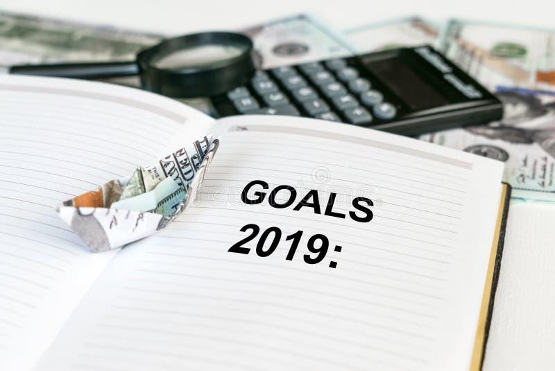 2019 celów tekst w otwartym notatniku z dolarowym banknotu origami statkiem, kalkulator, pieniądze i magnifier w tle, zdjęcie stock