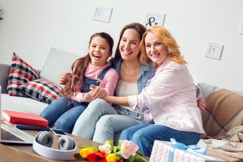Celebração da mãe e da filha da avó junto em casa que senta-se abraçando o riso alegre foto de stock royalty free
