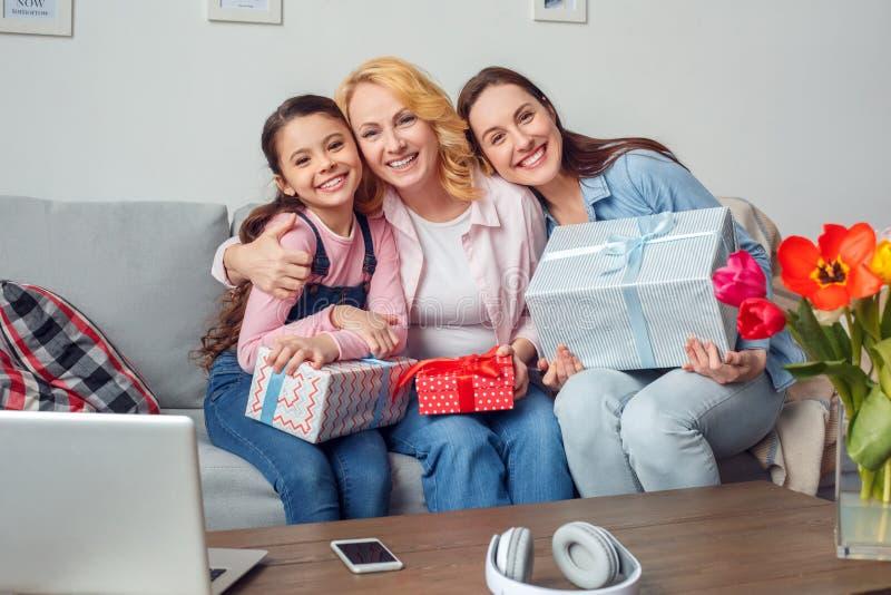 Celebração da mãe e da filha da avó junto em casa que senta-se com os presentes que abraçam o sorriso fotografia de stock