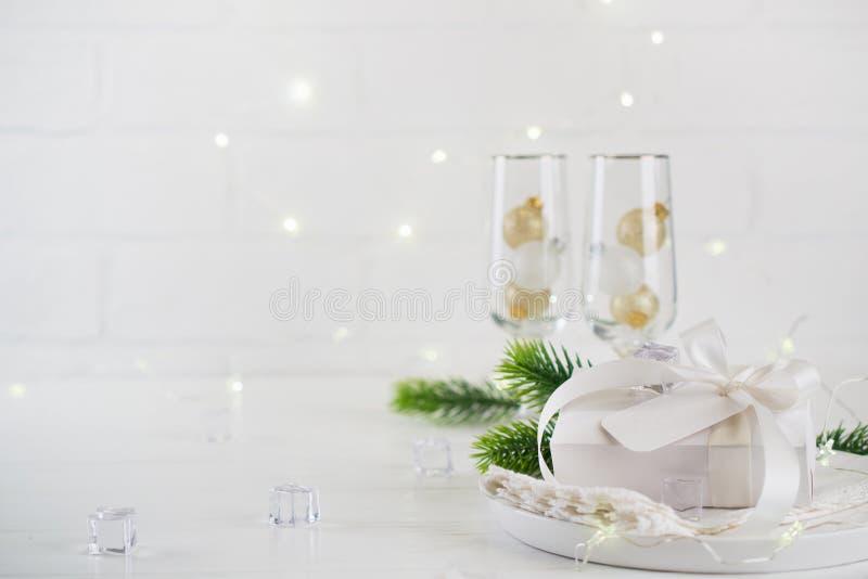Celebração do ano novo Ajuste de prata da tabela do Natal com dois vidros do champanhe na tabela e na caixa de presente de jantar imagens de stock royalty free