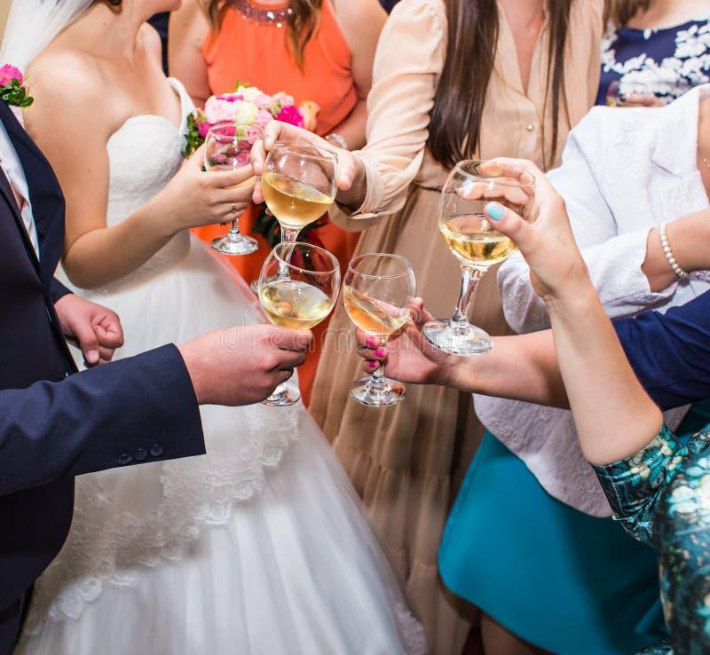 Celebração do casamento Mãos que guardaram os vidros da fatura do champanhe e de vinho um brinde imagens de stock