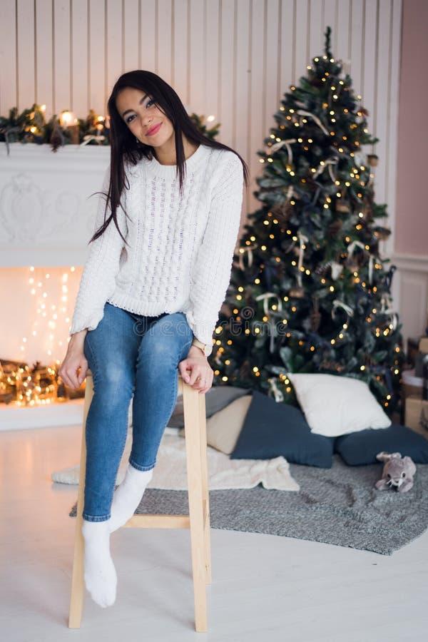 Celebração do Feliz Natal Jovem mulher surpreendente bonita no calças de ganga e sweather branco que sentam-se perto do Natal imagens de stock royalty free