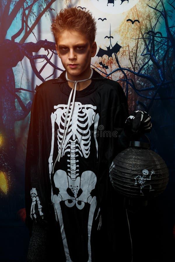 Celebração do feriado Dia das Bruxas, menino bonito na imagem, traje de 8 anos, o tema de esqueleto, vampiro, conceito do bastão fotografia de stock royalty free