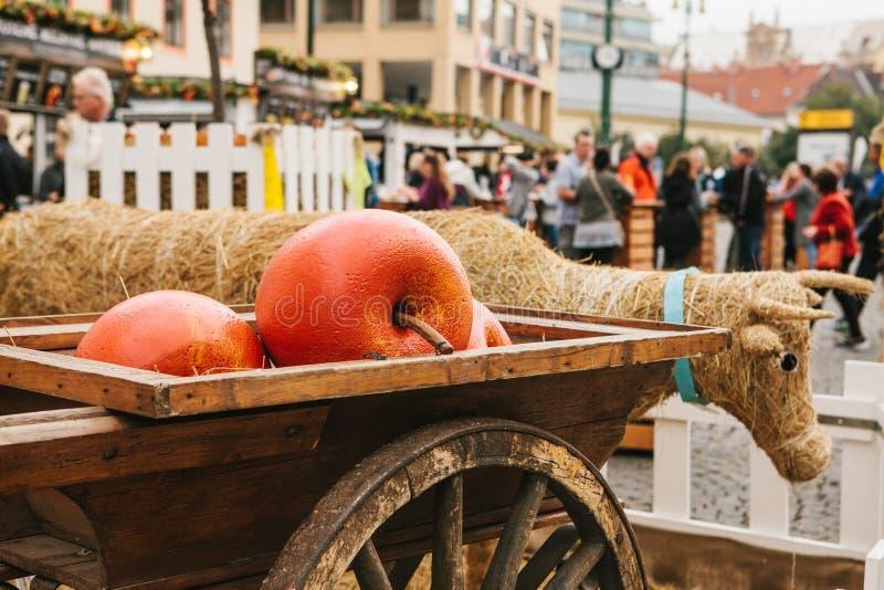 Celebração do mercado do tráfego da colheita do outono do quadrado de cidade com decorações Uma vaca da palha e umas maçãs decora imagem de stock royalty free