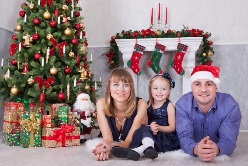 Celebração do Natal ou do ano novo Retrato de uma família feliz alegre de três povos que encontram-se no assoalho perto da árvore imagens de stock