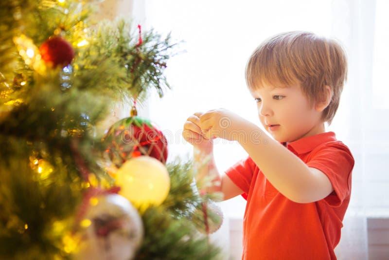 Celebração do partido do Xmas Criança que decora a árvore de Natal em casa A família com crianças comemora feriados de inverno Me fotografia de stock royalty free