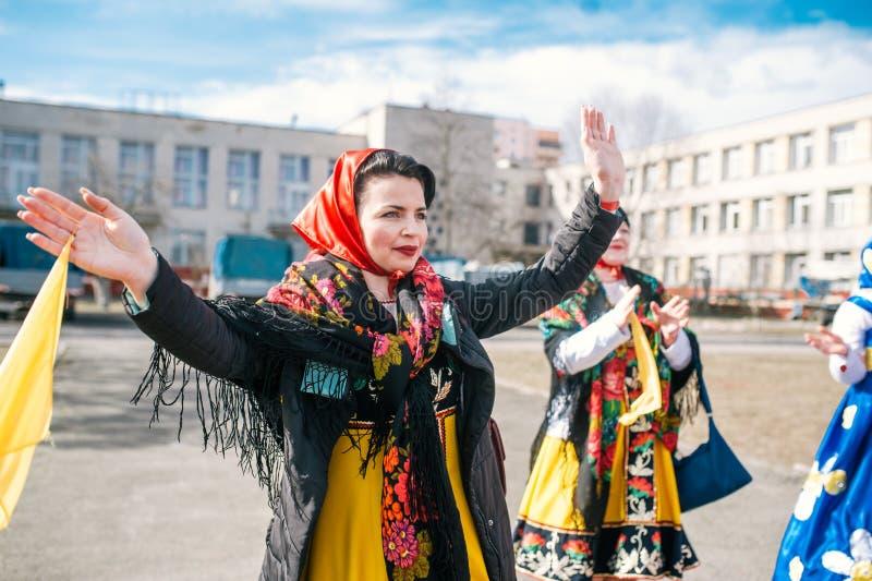 A celebração do Shrovetide na cidade Danças tradicionais e jogos em trajes populares imagens de stock