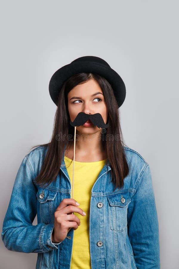Celebração e partido Tendo o divertimento a mulher bonita no chapéu está rindo Menina que veste os bigodes falsificados imagens de stock royalty free