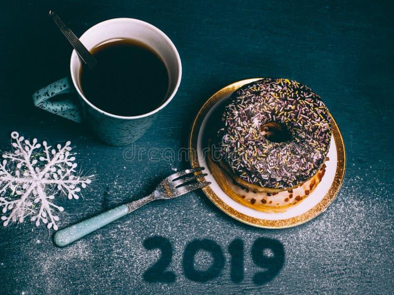 Celebração feliz do ano 2019 novo Xícara de café com filhós vitrificada fotos de stock