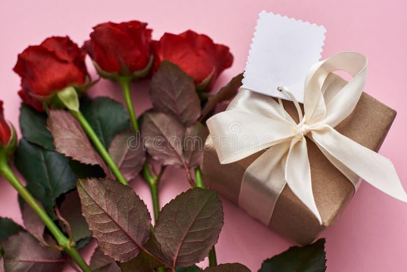 Celebração perfeita Vista ascendente próxima da caixa de presente no papel de envolvimento de kraft e em rosas vermelhas frescas foto de stock