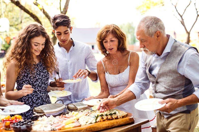 Celebración de familia o una fiesta de jardín afuera en el patio trasero imagenes de archivo