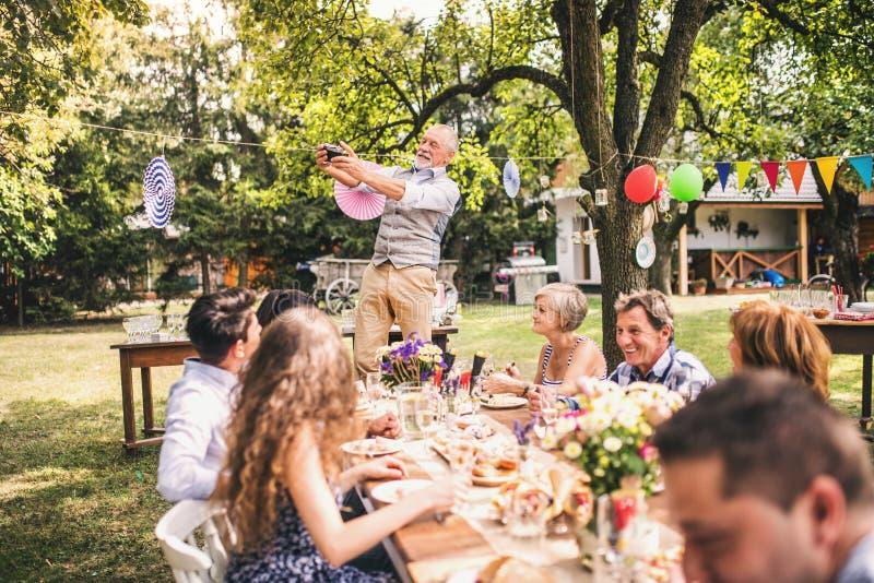 Celebración de familia o una fiesta de jardín afuera en el patio trasero fotografía de archivo