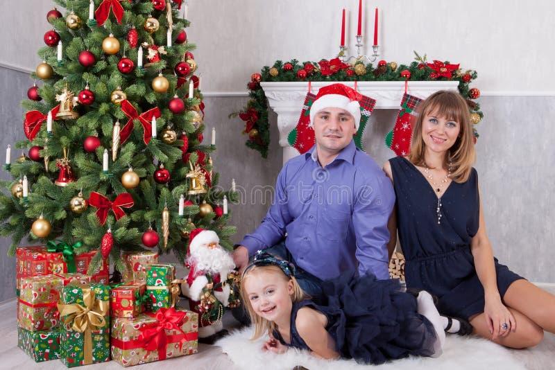 Celebración de la Navidad o del Año Nuevo Familia joven feliz en el árbol de navidad con una chimenea fotos de archivo