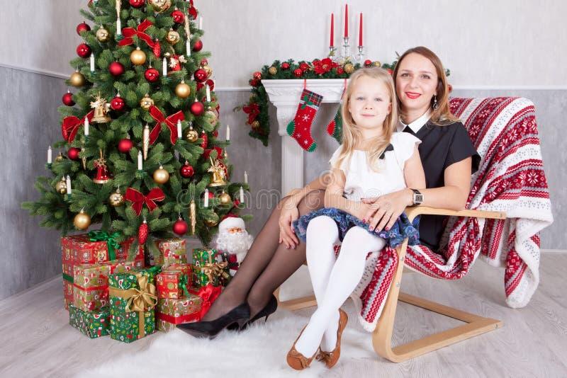Celebración de la Navidad o del Año Nuevo Madre feliz e hija que se sientan en silla cerca del árbol de navidad con los regalos d imagen de archivo libre de regalías