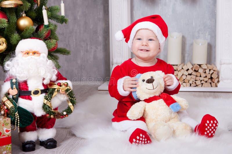 Celebración de la Navidad o del Año Nuevo La niña en vestido rojo y el sombrero de santa con el oso juegan sentarse en el piso ce imagen de archivo libre de regalías
