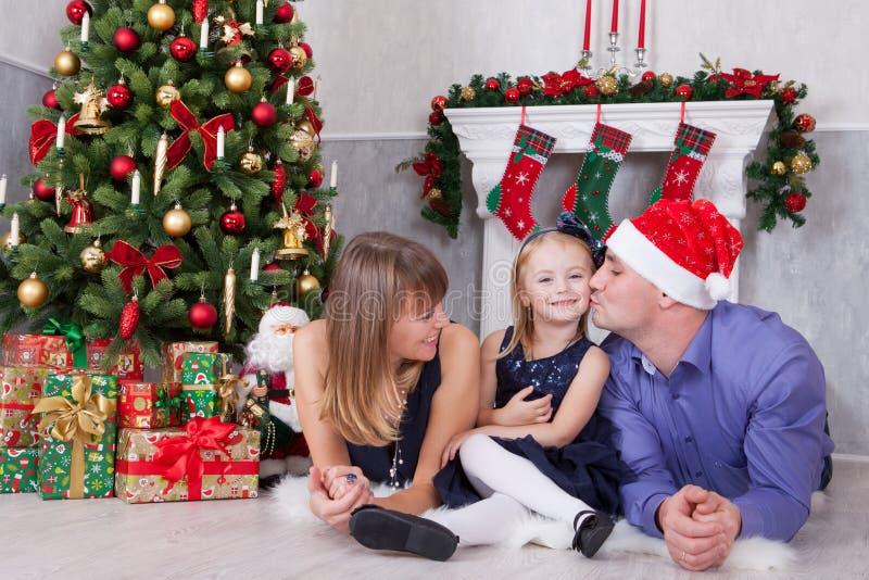 Celebración de la Navidad o del Año Nuevo Retrato de la familia feliz alegre de tres personas que mienten en el piso cerca del ár fotografía de archivo libre de regalías