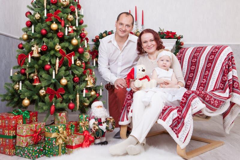 Celebración de la Navidad o del Año Nuevo Retrato de la familia joven alegre de tres personas cerca del árbol de navidad con los  fotografía de archivo