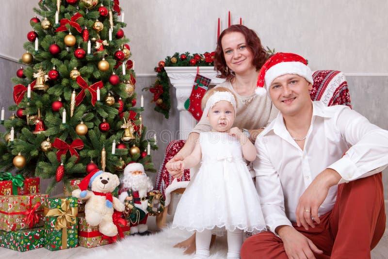 Celebración de la Navidad o del Año Nuevo Retrato de la familia joven alegre de tres personas cerca del árbol de navidad con los  fotos de archivo