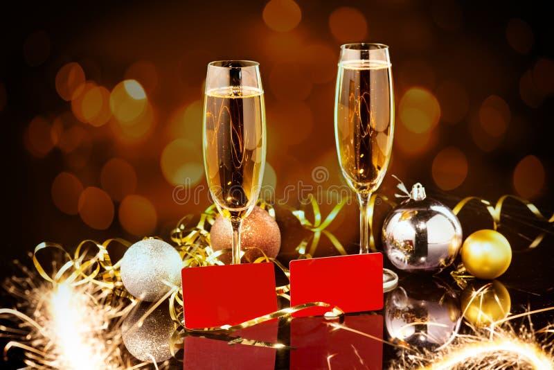 Celebración de la Navidad y del Año Nuevo con champán El día de fiesta del Año Nuevo adornó la tabla Dos vidrios del champán foto de archivo