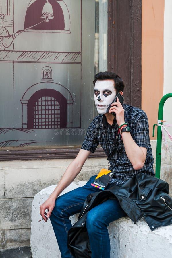Celebración del día de los muertos Un hombre disfrazado como esqueleto es que se sienta, que fuma y que habla en el teléfono móvi foto de archivo