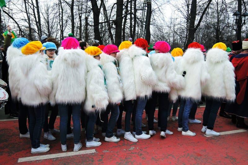 Celebración del día del ` s de St Patrick en Moscú Vestidos de las adolescencias en las capas mullidas blancas imagen de archivo