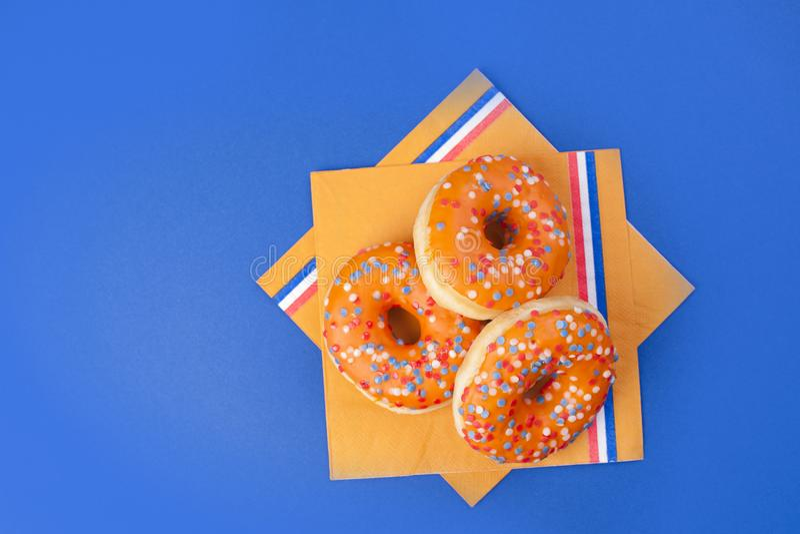 Celebración del día del ` s del rey en los Países Bajos Días de fiesta de la diversión Donats dulces anaranjados en un fondo azul imágenes de archivo libres de regalías