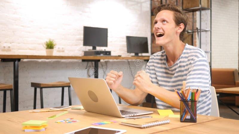 Celebración del hombre del éxito, emocionada y feliz que trabaja en oficina en el ordenador portátil fotos de archivo libres de regalías