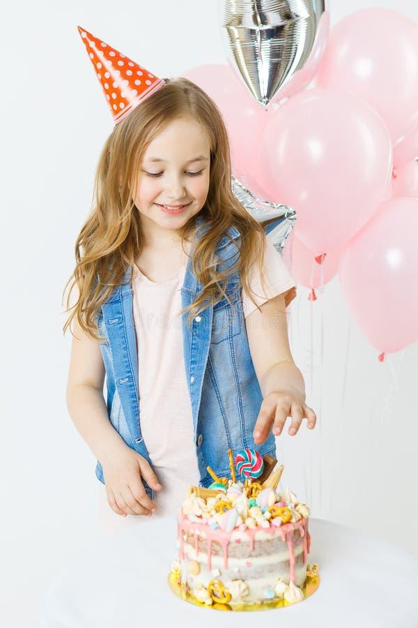celebración La pequeña muchacha rizada feliz en casquillo festivo se sienta cerca de la torta y de la sonrisa de cumpleaños Globo foto de archivo