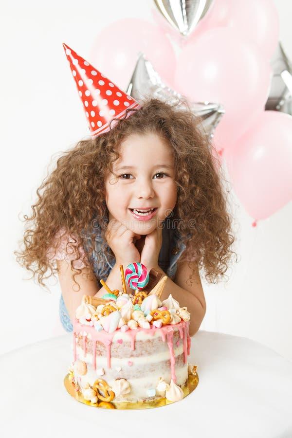 celebración La pequeña muchacha rizada feliz en taza festiva se sienta cerca de la torta y de la sonrisa de cumpleaños fotografía de archivo