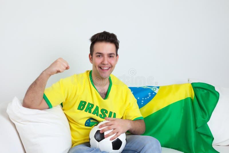 Celebraciones de la meta de un aficionado al fútbol brasileño en el sofá fotos de archivo