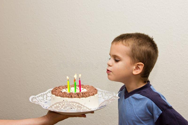 Celebrando il quinto ragazzo di compleanno agglutini la candela di salto del figlio fotografia stock