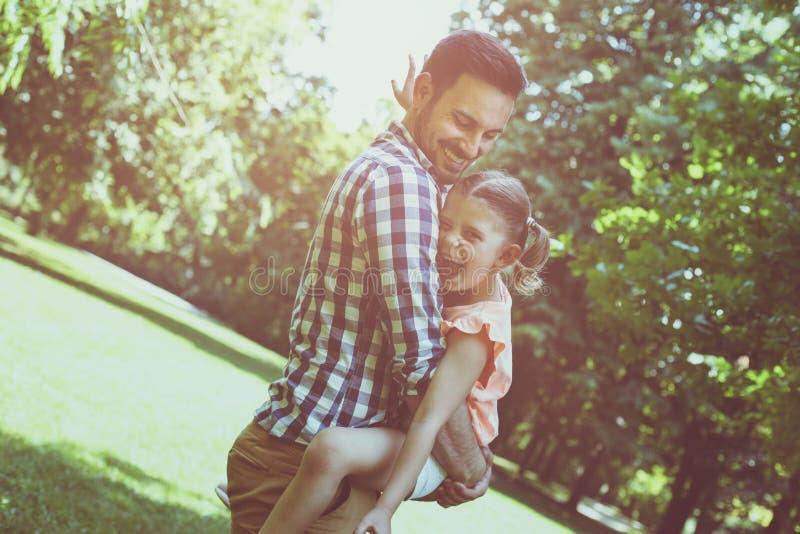 Celebrando su hija en sus brazos y la mirada de la cámara imagen de archivo libre de regalías