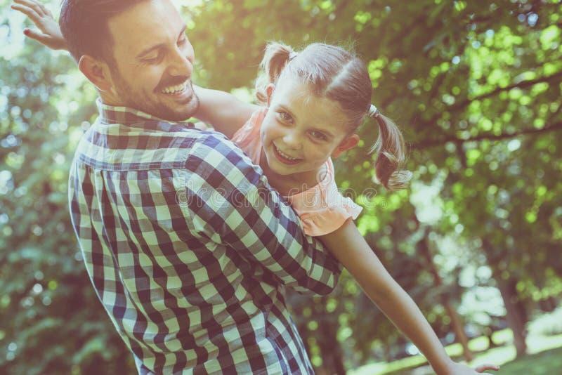 Celebrando su hija en sus brazos y la mirada de la cámara fotografía de archivo libre de regalías